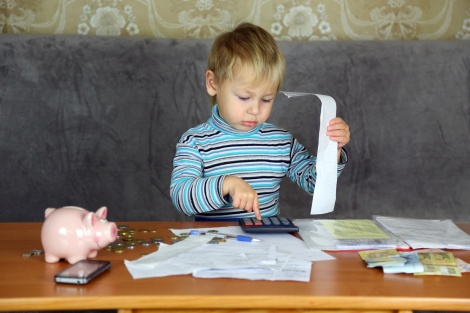little boy is engaged in home accounting and finance